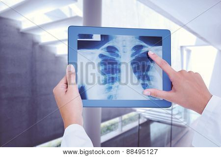 Doctor looking at xray on tablet against stylish modern home interior with staircase