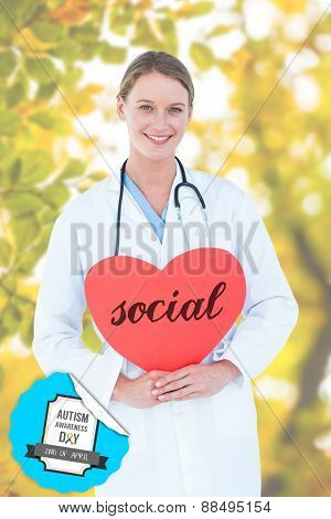 The word social and doctor holding red heart card against detail shot of leaves