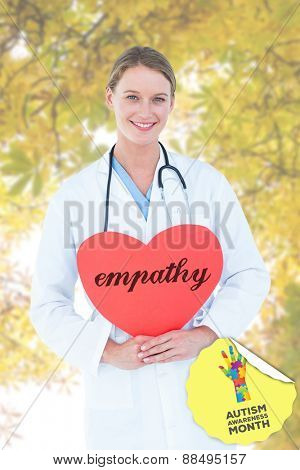 The word empathy and doctor holding red heart card against autumnal leaves against the clear sky