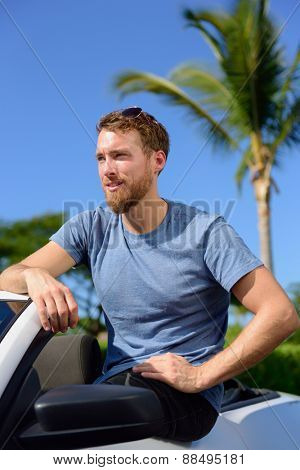 Handsome man showing off new luxury cabriolet car. Portrait of confident Caucasian young male in his 20s owner of a grey convertible car, purchase or rental. Summer road trip concept.