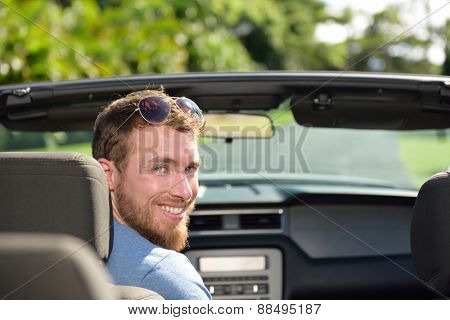 Car driver man driving convertible on a road trip. Portrait of a young Caucasian male adult looking at camera in his new or rental automobile happy to travel on holiday for summer vacations.