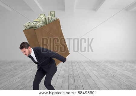 Businessman carrying something heavy with his back and hands against big room with white wall