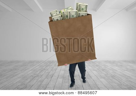 Businessman carrying something heavy with his hands against big room with white wall