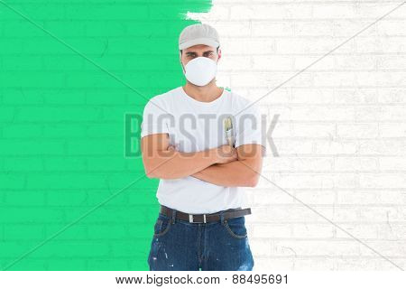 Man with paintbrush standing arms crossed by ladder against white wall