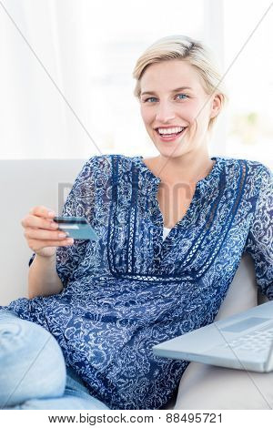 Pretty blonde woman doing online shopping in the living room