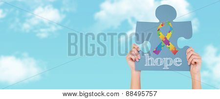 Hands showing jigsaw puzzle against blue sky