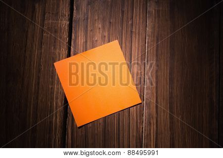 Orange post it on wooden background