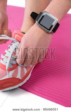 Woman tying her laces of sport shoes on pink exercise mat
