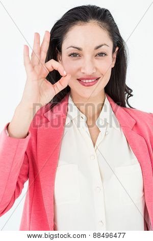Smiling brunette doing okay sign on white background