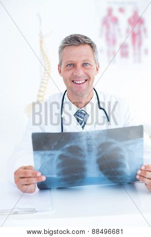 Smiling doctor holding xray in medical office