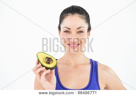 Pretty woman showing half of an avocado on white background
