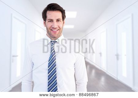 Smiling businessman standing with hands in pockets against bright hallway with several doors