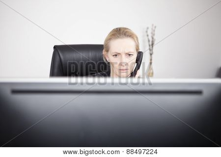 Serious Businesswoman On Phone Looking At Monitor