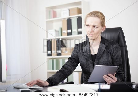 Serious Manageress Looking At Her Desktop Monitor