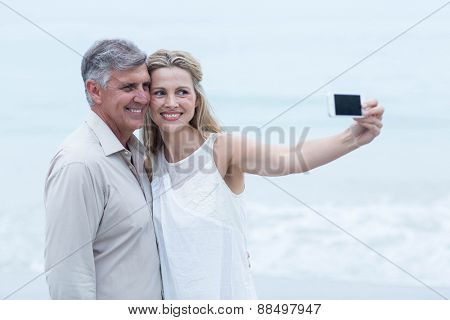 Happy couple taking a selfie at the beach