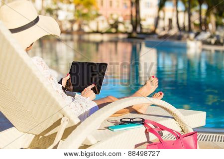 Woman using laptop computer by the swimming pool