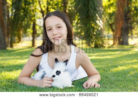 Cute Beautiful Smiling Teen Girl On Grass With White And Black Rabbit