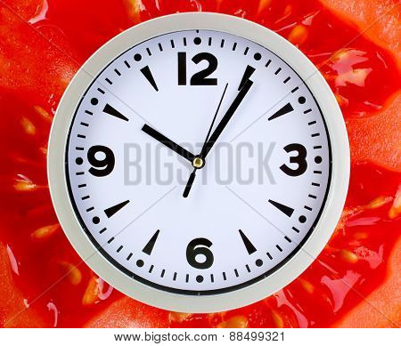 Food clock with tomato as background. Healthy food concept