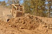 picture of bulldozers  - Large bulldozer moving rock and soil for fill for a new commercial development road construction project - JPG