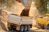 stock photo of dump_truck  - Large track hoe excavator filling a dump truck with rock and soil for fill for a new commercial development road construction project - JPG