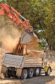 picture of track-hoe  - Large track hoe excavator filling a dump truck with rock and soil for fill for a new commercial development road construction project - JPG