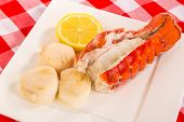 picture of scallop shell  - Three poached scallops on square white plate with steamed lobster tail with shell split and large slice of lemon - JPG