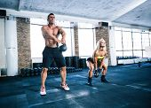 image of kettles  - Group of a man and woman workout with kettle ball at gym - JPG