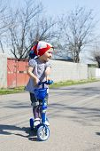 picture of tricycle  - Beautiful baby girl rides tricycle in summer - JPG