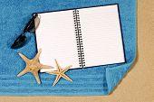 foto of starfish  - Beach scene with starfish towel sunglasses and blank writing book - JPG