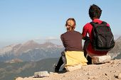 Couple Sitting And Looking Over Mountains poster