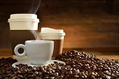 pic of coffee crop  - Cups of coffee with smoke and coffee beans on old wooden background - JPG
