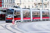 foto of tram  - Modern red tram making turn at ringstrasse street at the center of Vienna - JPG