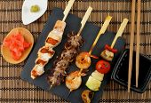 foto of soy sauce  - Grilled Salmon Octopuses Shrimps and Vegetables on Wooden Stick with Ginger Soy Sauce and Wasabi on Straw Mat background - JPG
