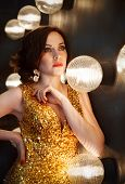 image of superstars  - Superstar woman wearing golden shining dress posing - JPG