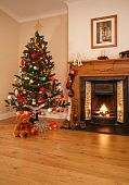 stock photo of cozy hearth  - Living room with christmas decorations a fireplace and christmas tree - JPG
