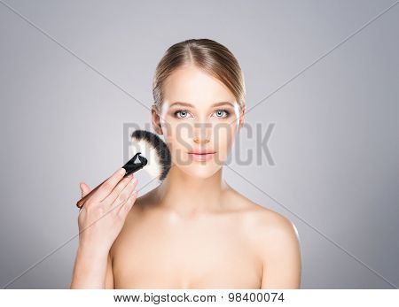 Attractive young woman applying powder on her cheeks.