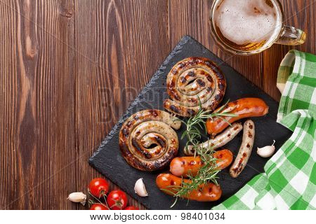 Grilled sausages and beer mug on wooden table. Top view with copy space