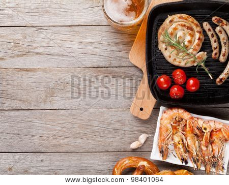 Beer mug, grilled shrimps, sausages and pretzel on wooden table. Top view with copy space