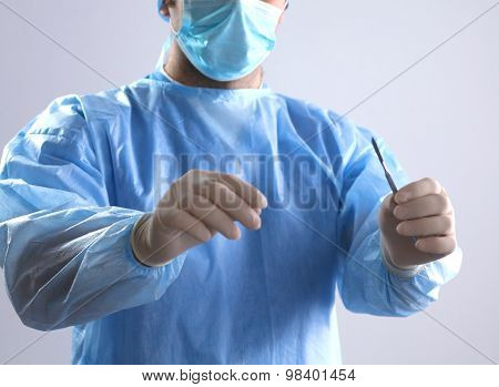 Man surgeon holds a scalpel in an operating room