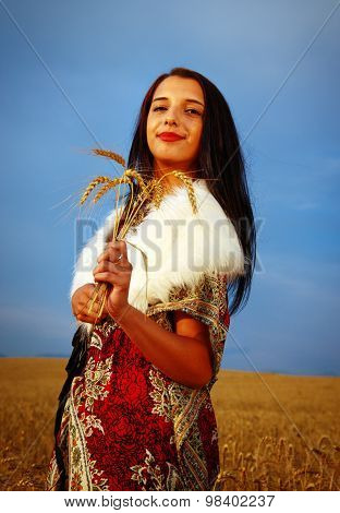 Young woman with ornamental dress and white fur standing on a wheat field with sunset. Natural backg