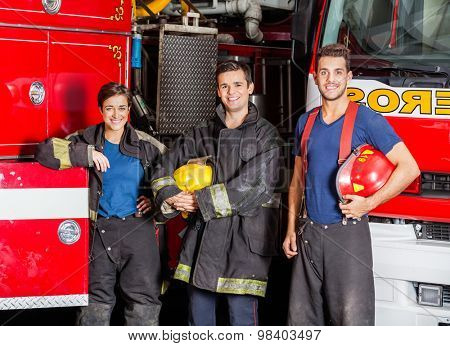 Portrait of confident young firefighters standing against trucks at fire station