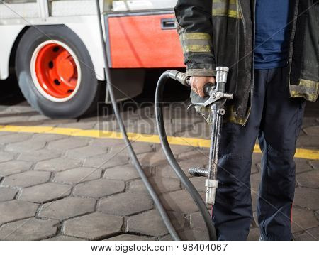 Midsection of firefighter holding water hose while standing at fire station