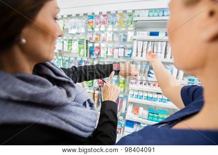 Mid adult female customer showing smartwatch to pharmacist in drugstore