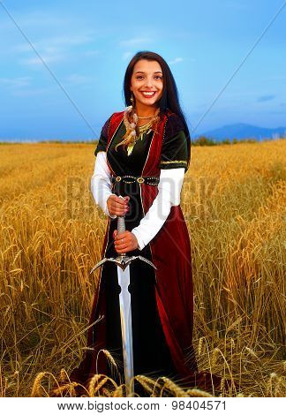 Smiling Young woman with ornamental dress and sword in hand  standing on a wheat field with sunset.