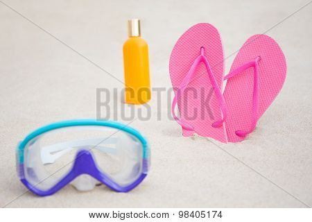 Close Up Of Diving Mask, Flip Flops And Suntan Lotion Bottle On Sandy Beach