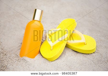 Summer And Skin Care Concept - Slippers And Suntan Lotion Bottle On Sandy Beach