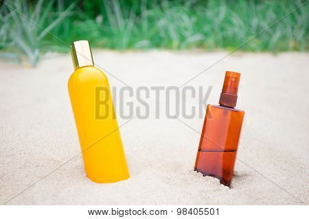 Suntan Lotion And Spray Bottles On Sandy Beach