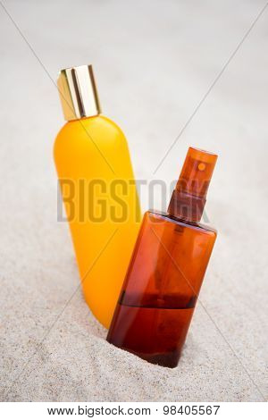 Sunbathing Concept -suntan Lotion Bottles In Sand