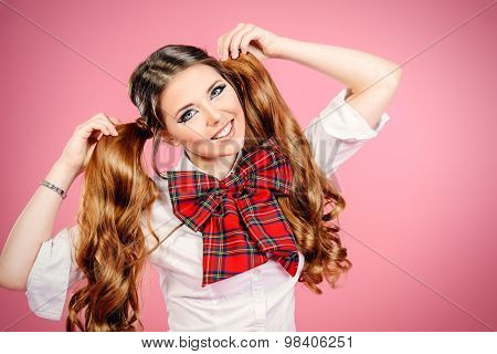 Portrait of a pretty smiling teen girl in school uniform posing over pink background. Anime style.