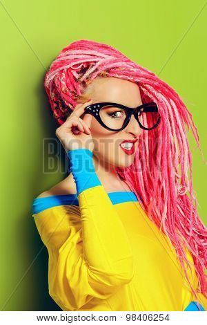 Modern pin-up girl in bright clothes and pink dreadlocks. Disco, party. Bright fashion.